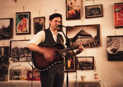 Hochzeitssänger Hamburg Cedric Saga Live mit Gitarre vor Bilderwand